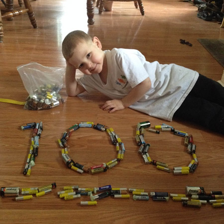A student poses with the 100 batteries he recycled.