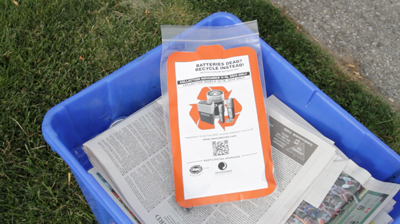 Battery recycling bag sits on top of a blue box during fall curbside collections