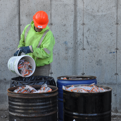 GFL staff empties full pails of batteries into consolidation drums