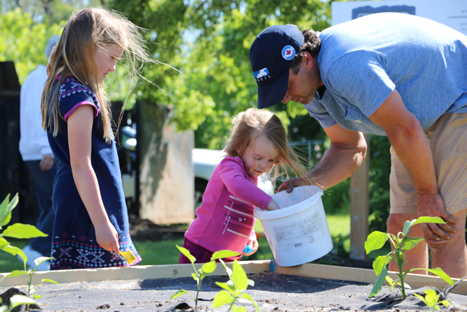 Jordan Elliott of Marine Recycling Corporation helps a youngster plant seedlings at the Lockview Park Community Garden in Port Colborne in support of the Port Cares Food Bank.