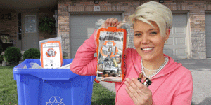 A resident holds up her battery recycling bag filled with household batteries