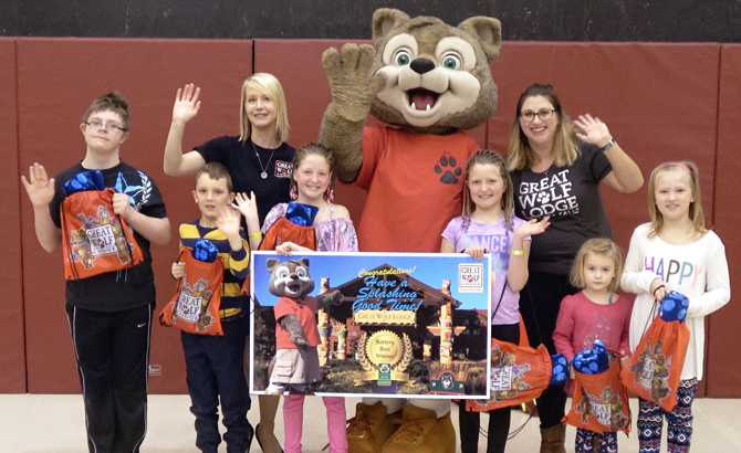 Sarah Lacharity of Raw Materials Company along with Wiley the Wolf pose for a picture with the six Battery Bosses from Montgomery Village Public School. Pictured from left to right; Darby, Ryder, Jillian, Jordan, Claudia and Anika.