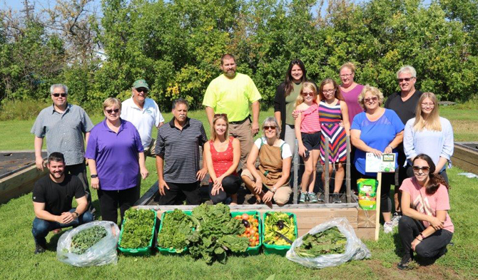 Employees from Raw Materials Company pose for a picture in front of the produce they harvested from the Iron Earth Community Garden in Port Colborne Ontario.