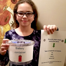 An OSBRC student holds up her battery recycling container and poster she made to complete mission 1