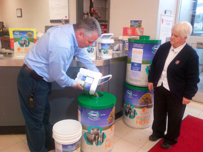 Todd Black from the Sault Saint Marie, Ontario Canadian Tire fills the first drum of recycled batteries as Mildred Brodie from the Salvation Army Food Bank looks on.