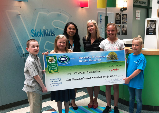 Students from the Ontario Schools Battery Recycling Challenge by Raw Materials Company pose for a picture with a giant cheque at the SickKids Foundation in Toronto.